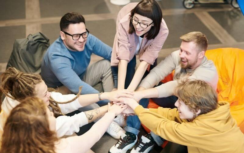 Des collègues qui tendent les bras et communient joyeusement vers le même objectif, la force du collectif